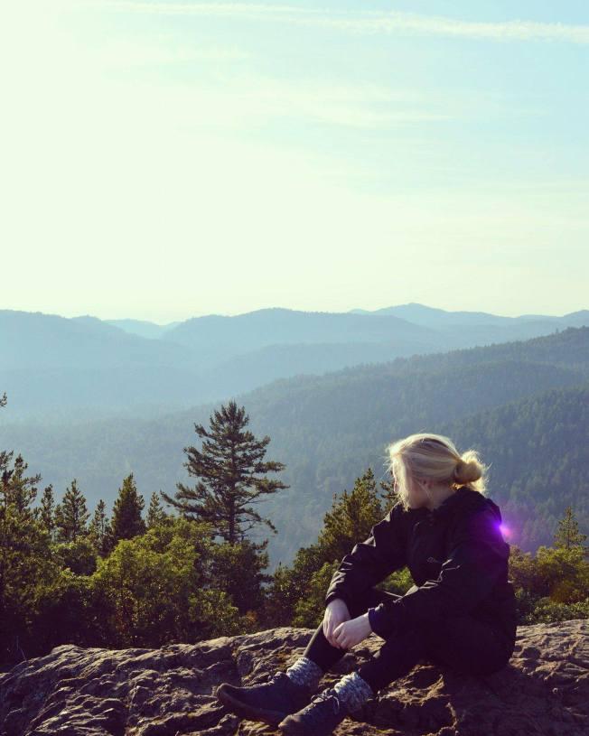 A rocky outcrop overlooking green hills