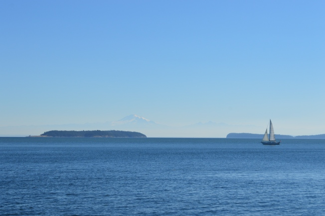 A sail boat on the ocean with a mountain in the background